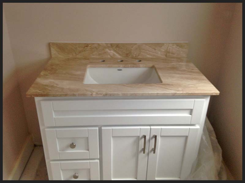 Daino Realle Marble bathroom counter with white cabinet.