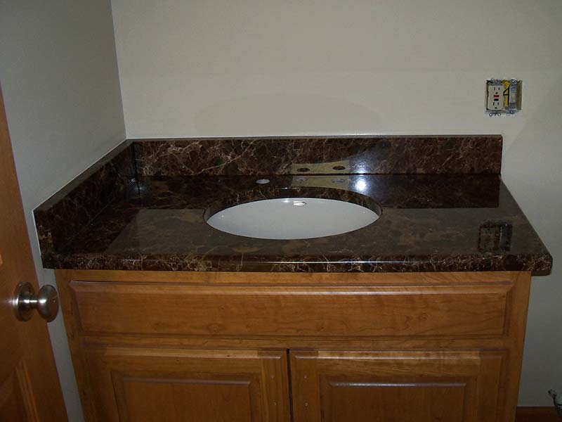 Emperador Dark Marble bathroom counter over medium toned bathroom vanity.