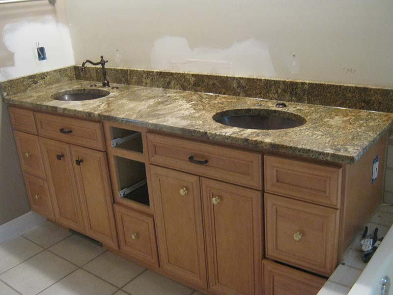 Juperana Persa bathroom counter with double sinks and oiled bronze faucets over light wood cabinets.