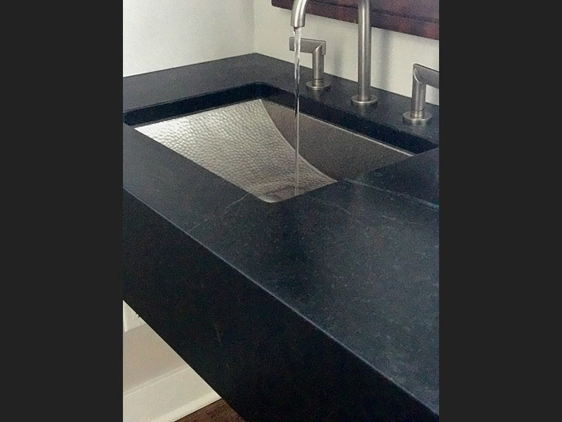 Oiled Black Soapstone Bathroom Counter With A Hammered Metal Sink.