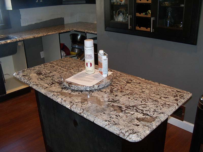 Lennon Granite sideboard cabinet coordinates with the Lennon Granite kitchen counters surrounded by dark wood cabinets.