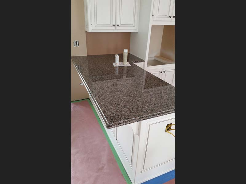 Caledonia Granite kitchen counter contrasting with light colored cabinets.