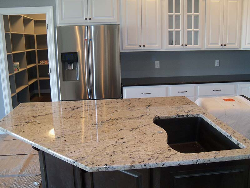A close up of the cut out for the sink in this Delicatus Granite kitchen island counter.