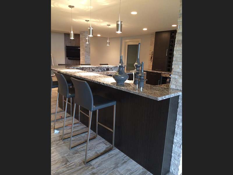 Diamond Wave Granite bar with dark wood cabinets.