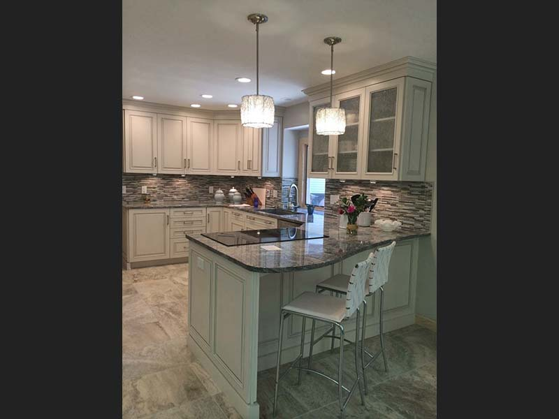 Diamond Wave Granite accentuates this counter top range surrounded by white cabinets and a neutral backsplash.