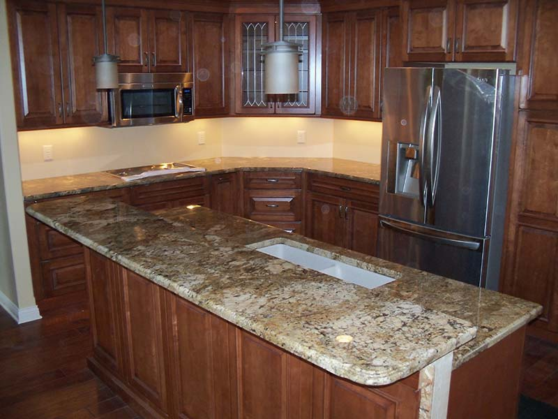 The Juperana Persa Granite kitchen counters and island just jump out against the warm toned wood cabinets.