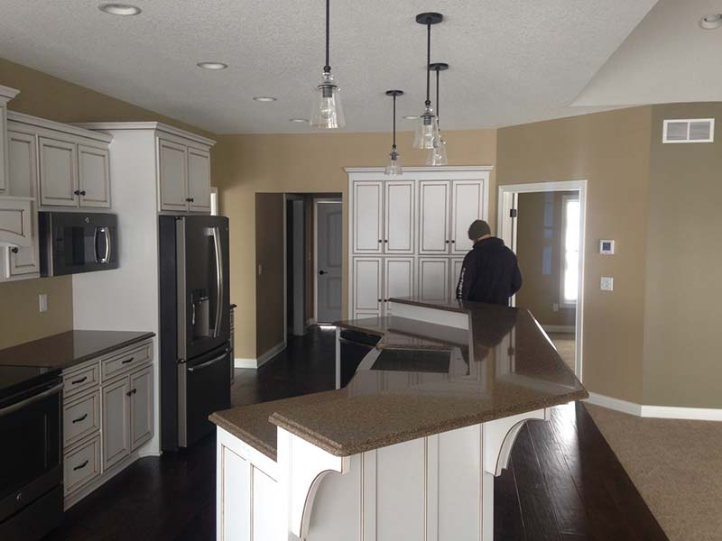 Quartz kitchen island surround by white cabinets and earthtone walls.