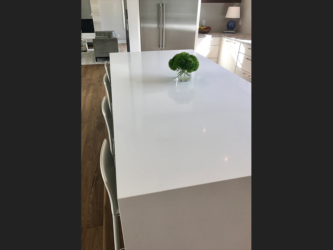 Royale Blanc Quartz Island with waterfall leg.  The counter tops are Honed Superwhite Marble.