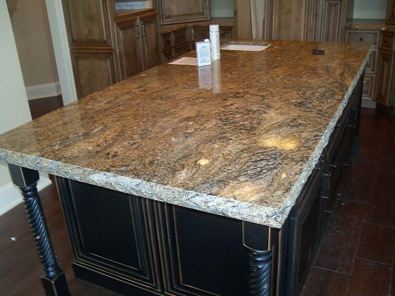 Stormy Night Granite over a dark kitchen island surrounded by medium wood toned cabinets.
