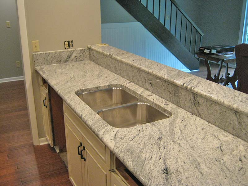Viscont white Granite kitchen island with stainless steel double sink.