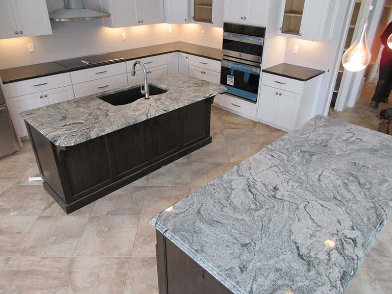 Viscont white Granite kitchen islands contrasting with dark granite counters.