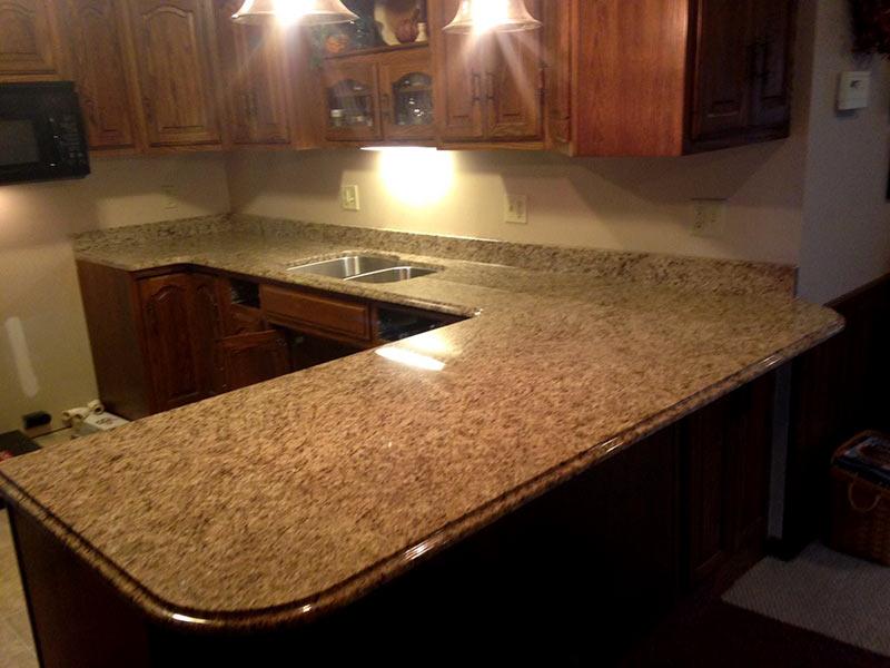 Earthtones Create A Warm Inviting Kitchen With Giallo Ornamental Granite And Medium Brown Cabinets